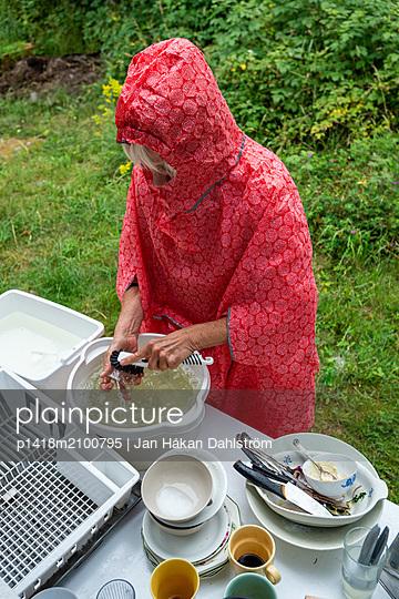 Frau in Regenmantel wäscht das Geschirr im Freien ab - p1418m2100795 von Jan Håkan Dahlström