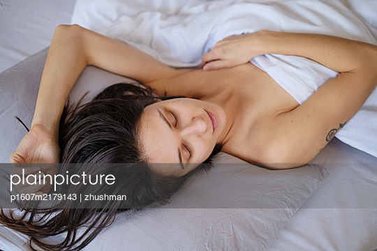 Young woman sleeping in her bed - p1607m2179143 by zhushman
