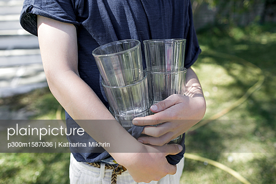 Boy standing in garden holding empty glasses, partial view - p300m1587036 von Katharina Mikhrin