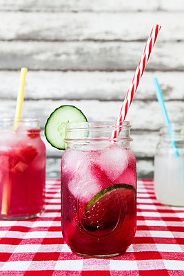 Summer cocktails in glass jars on tablecloth - p1094m1015336 by Patrick Strattner