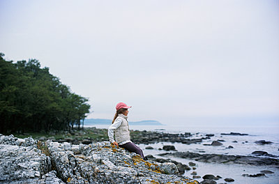 Girl with baseball cap looks at the sea, Sweden - p1481m2203814 by Peo Olsson