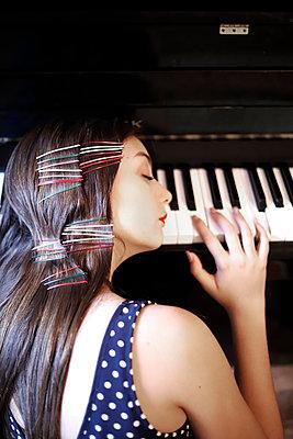 Junge Frau lehnt auf dem Klavier - p1521m2128965 von Charlotte Zobel