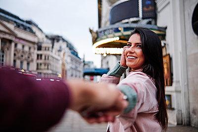 Happy young woman holding hand of boyfriend n city - p300m2273669 by Angel Santana Garcia