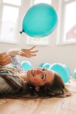 Young woman in new apartment playing with balloons - p586m1064901 by Kniel Synnatzschke