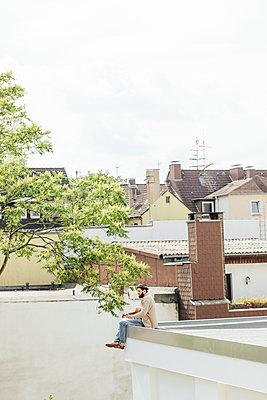 Junger Mann liegt mit einer Gitarre auf dem Dach - p586m919094 von Kniel Synnatzschke