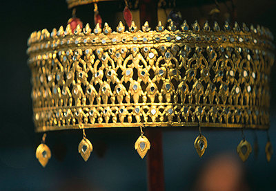 Nahaufnahme eines goldenen Schirmes in einem buddhistischen Tempel - p9791608 von Heyens