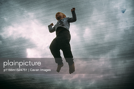 Low angle view of boy jumping on trampoline against cloudy sky - p1166m1524751 by Cavan Images