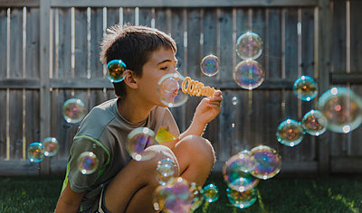 Boy blowing bubbles while crouching at backyard - p1166m2112105 by Cavan Images