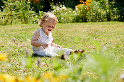 Toddler boy playing in the grass in the sunshine - p1540m2289802 by Marie Tercafs