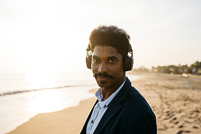 Afro man with headphones at beach during sunny day - p300m2266993 by Josep Rovirosa