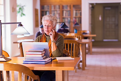 Older mixed race woman using laptop in library - p555m1306131 by Marc Romanelli