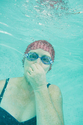 Woman underwater holding nose looking at camera - p597m2008077 by Tim Robinson