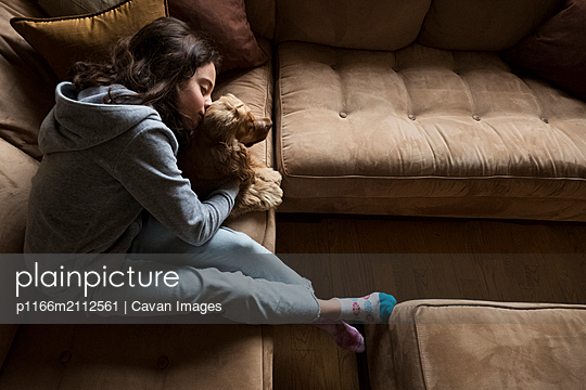 High angle view of girl kissing Cocker Spaniel while relaxing on sofa at home - p1166m2112561 by Cavan Images