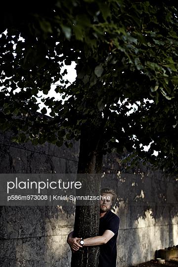 Ein Mann umarmt einen Baum - p586m973008 von Kniel Synnatzschke