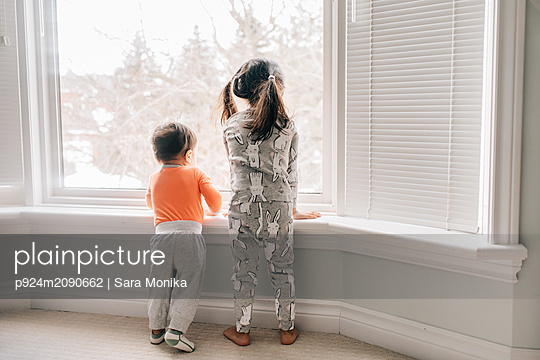 Girl and baby brother looking through living room window, rear view - p924m2090662 by Sara Monika