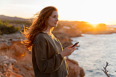 Redheaded young woman with cell phone at the coast at sunset, Ibiza, Spain - p300m2159919 von VITTA GALLERY