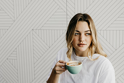 Young woman looking away while drinking coffee in cafe - p300m2226017 by letizia haessig photography