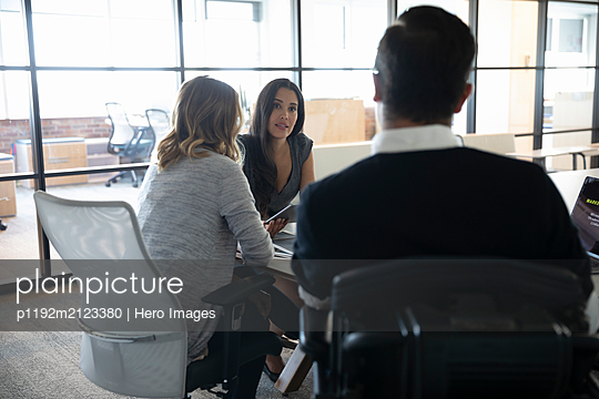 Businessman in wheelchair listening to colleagues in meeting - p1192m2123380 by Hero Images