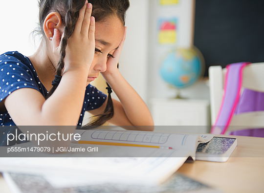 Mixed race girl studying in classroom - p555m1479079 by JGI/Jamie Grill
