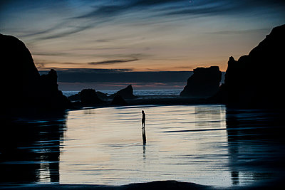 Mid distance view of silhouette person standing at Bandon Beach - p1166m1489326 by Cavan Images