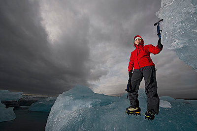 woman climbing iceberg on the south coast of Iceland using ice pick - p1166m2269498 by Cavan Images