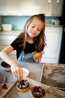 pretty girl bakes donuts with chocolate and sprinkles in modern kitchen, lower austria - p300m2180228 von Epiximages