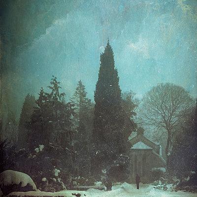 Person standing in front of snowy graveyard chapel - p300m2219194 by Dirk Wüstenhagen