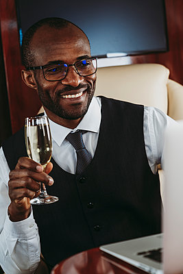 Smiling male entrepreneur with champagne working on laptop in private jet - p300m2257049 by OneInchPunch