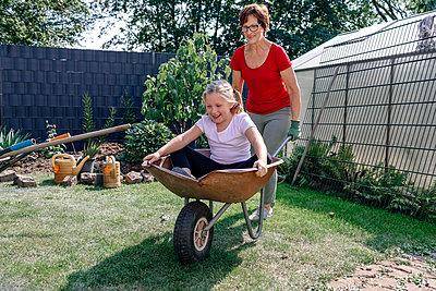Happy girl sitting in wheelbarrow while playing with grandmother at backyard - p300m2276115 by Oxana Guryanova