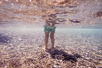 Underwater view of Caucasian girl standing in ocean - p555m1411181 by Alberto Guglielmi