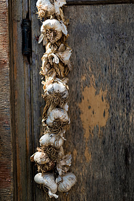 A garlic plait is hung up to dry over a wooden door - p1433m1584188 by Wolf Kettler