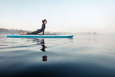 Woman practicing paddle board yoga on lake Kirchsee in the morning, Bad Toelz, Bavaria, Germany - p300m2156881 by Wilfried Feder