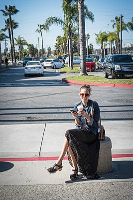 Caucasian woman sitting on concrete barrier in parking lot - p555m1410011 by Alberto Guglielmi