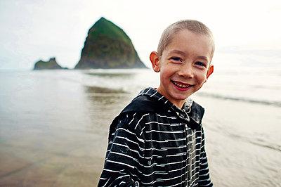 Portrait of happy boy standing at beach against sky - p1166m1415127 by Cavan Images