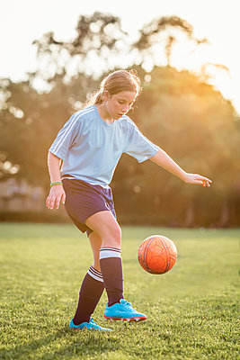 Girl kicking soccer ball while playing at field - p1166m1541890 by Cavan Social