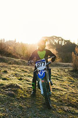 Motocross driver standing on circuit at sunset - p300m2103193 by Francesco Buttitta