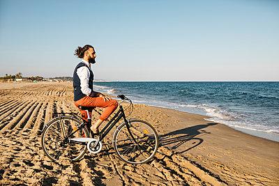 Well dressed man with his bike on a beach - p300m2132026 by Josep Rovirosa