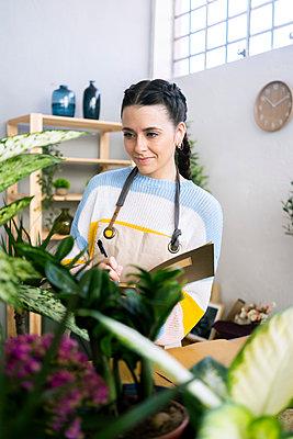 Young woman working in a gardening laboratory or plant shop - p300m2275350 von Giorgio Fochesato