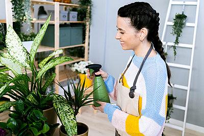 Young woman working in a gardening laboratory or plant shop - p300m2275394 von Giorgio Fochesato
