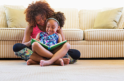 Mixed race mother and daughter reading book on floor near sofa - p555m1521340 by Don Mason