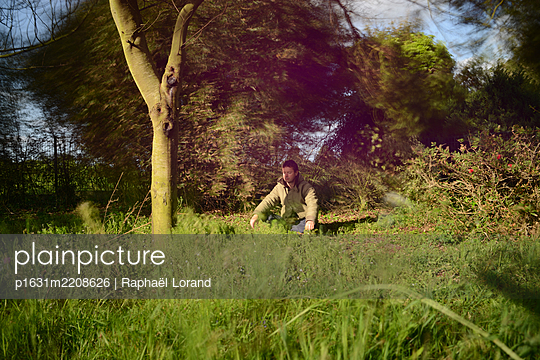 Man meditating in the grass  - p1631m2208626 by Raphaël Lorand