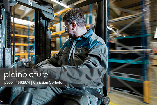 plainpicture - plainpicture p300m1562874 - Fork-lift driver in motion ... - plainpicture/Westend61/Christian Vorhofer