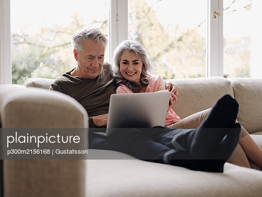Happy senior couple with laptop relaxing on couch at home - p300m2156168 by Gustafsson