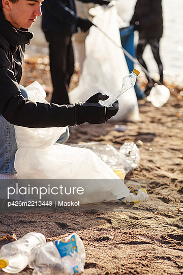 Young male environmentalist collecting plastic bottle by lake - p426m2213449 by Maskot