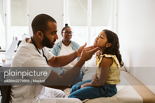 Male doctor examining throat of girl while sitting in medical clinic - p426m2279866 by Maskot
