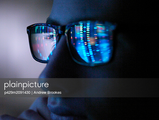 Genetic research, computer screen reflection in spectacles of DNA profile, close up of face - p429m2091430 by Andrew Brookes