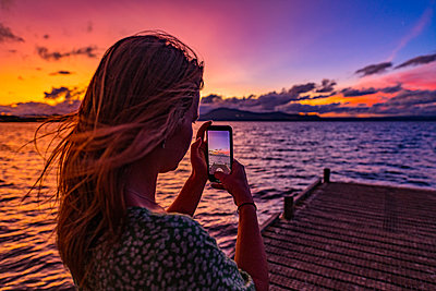 Woman with smartphone takes picture of sunset - p1455m2204884 by Ingmar Wein