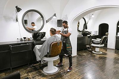 Barber cutting hair of a customer in barber shop - p300m2113934 von Hernandez and Sorokina