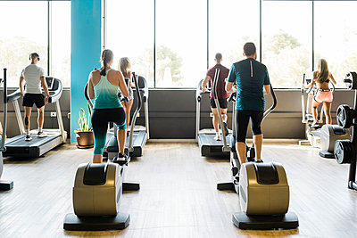 Men and women on exercise machines at gym - p300m2286621 by Manu Padilla Photo