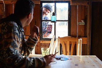 Man showing photograph over smart phone to friend sitting in cottage - p426m2117226 by Maskot
